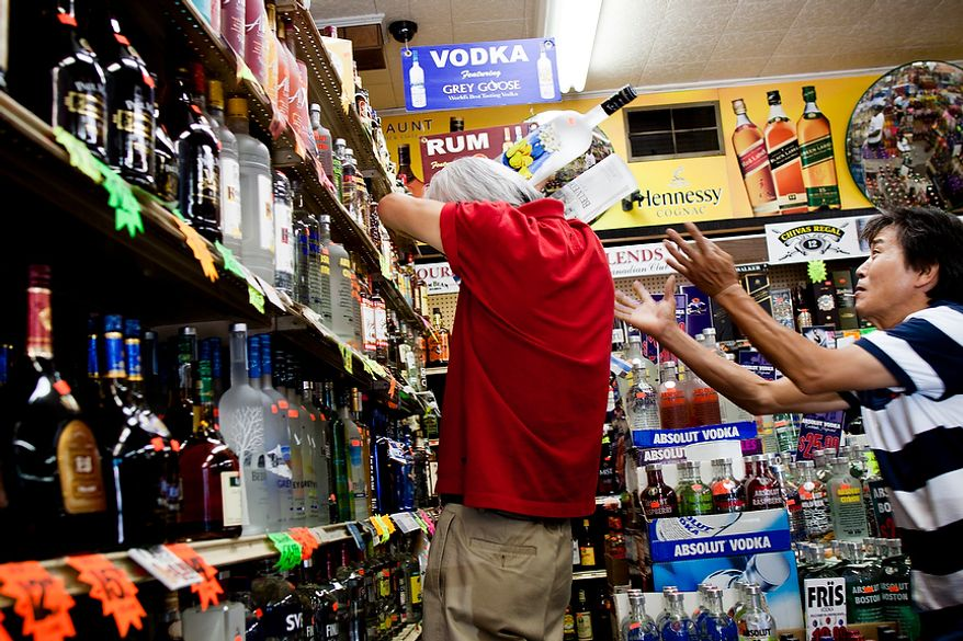 Sung Kim, right, employee at Sammy's Liquor in Northeast Washington, D.C., gives support to store owner, Dae Yoon, as he tries to re-rack several glass bottles of liquor that were dislodged during a 5.9 magnitude earthquake in the District on Tuesday, August 23, 2011. (Pratik Shah/The Washington Times)