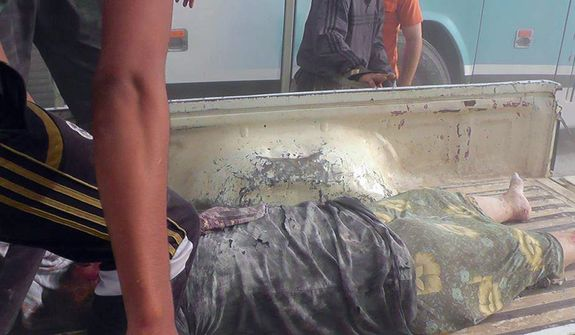 In this Wednesday, Oct. 17, 2012 photo, citizen journalism image provided by Edlib News Network, ENN, which has been authenticated based on its contents and other AP reporting, the dead body of Syrian woman lies on the back of a pickup truck after she was removed from under the rubble of a building that was destroyed from a Syrian force airstrike, at Kfar Nebel town, in Idlib province, northern Syria. (AP Photo/Idlib News Network ENN)