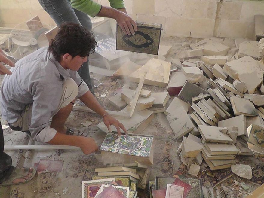 In this Wednesday, Oct. 17, 2012 photo, citizen journalism image provided by Edlib News Network, ENN, which has been authenticated based on its contents and other AP reporting, Syrian citizens remove copies of the Quran, the Muslims holy book from under the rubble of a destroyed mosque that was destroyed due to government forces shelling, at Kfar Nebel town, in Idlib province, northern Syria. (AP Photo/Idlib News Network ENN)