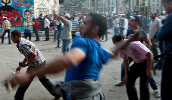 Protesters throw stones after scuffles broke out between groups of protesters in Tahrir square when chants against the new Islamist president angered some in the crowd in Cairo, Egypt, Friday, Oct. 12, 2012. Thousands of supporters and opponents of Egypt's new Islamist president clashed in Cairo's Tahrir Square on Friday, hurling stones and concrete and swinging sticks at each other in the first such violence since Mohammed Morsi took office more than three months ago. (AP Photo/Khalil Hamra)