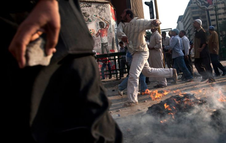 A protester throws a stone after scuffles broke out between groups of protesters in Tahrir square when chants against the new Islamist president angered some in the crowd in Cairo, Egypt, Friday, Oct. 12, 2012. Thousands of supporters and opponents of Egypt's new Islamist president clashed in Cairo's Tahrir Square on Friday, hurling stones and concrete and swinging sticks at each other in the first such violence since Mohammed Morsi took office more than three months ago. (AP Photo/Khalil Hamra)