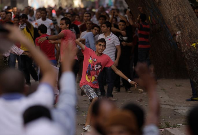 A protester throws a stone after scuffles broke out between groups of several hundred protesters in Tahrir square when chants against the new Islamist president angered some in the crowd in Cairo, Egypt, Friday, Oct. 12, 2012. The scuffles between supporters and opponents of President Mohammed Morsi reflect deep political divisions among the countryís 82 million people, more than a year after the popular uprising that toppled Hosni Mubarak. (AP Photo/Khalil Hamra)