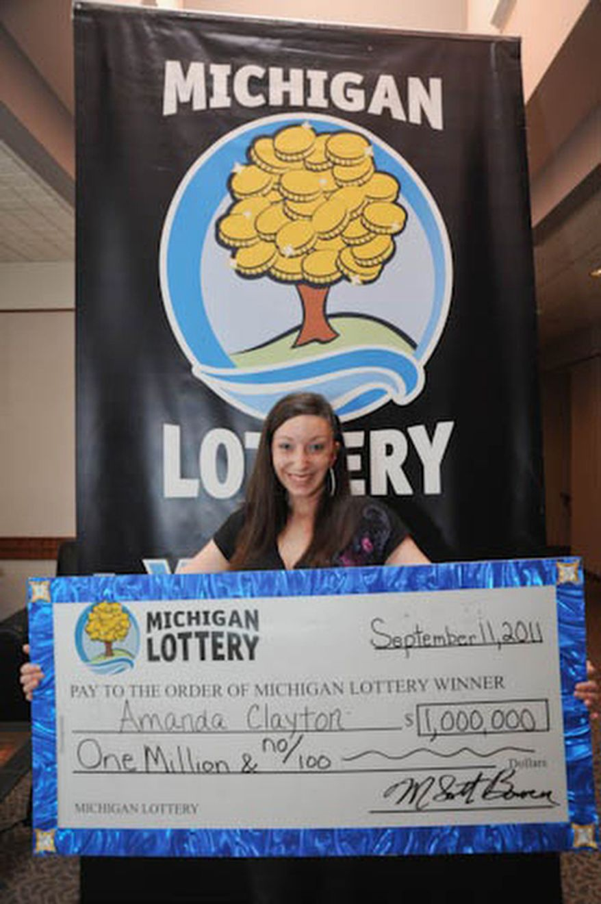 In this photo provided by the Michigan Lottery, Amanda Clayton holds her $1 million lottery check. The state says Clayton who won a $1 million lottery prize but continued to get food stamps has been removed from a food assistance program. (AP Photo/Courtesy Michigan Lottery via Detroit Free Press)  DETROIT NEWS OUT; AOL OUT