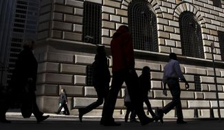 **FILE** Pedestrians walk past the Federal Reserve Bank in New York on Oct. 18, 2012. (Associated Press)