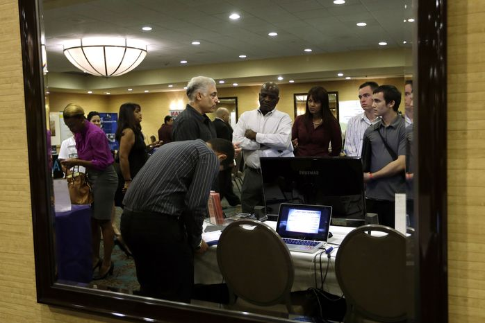 **FILE** Robert Orkin (third from left) of the company TxT-Alert talks with job seekers during a Sept 17, 2012, job fair held by National Career Fairs in Fort Lauderdale, Fla. (Associated Press)