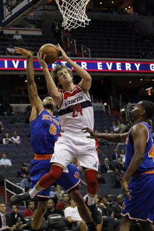 Washington Wizards forward Jan Vesely (24), of the Czech Repulbic, goes to the basket between New York Knicks forward Kurt Thomas, right, and center Tyson Chandler (6)during the first quarter of an NBA preseason basketball game in Washington, Thursday, Oct. 11, 2012. (AP Photo/Ann Heisenfelt)