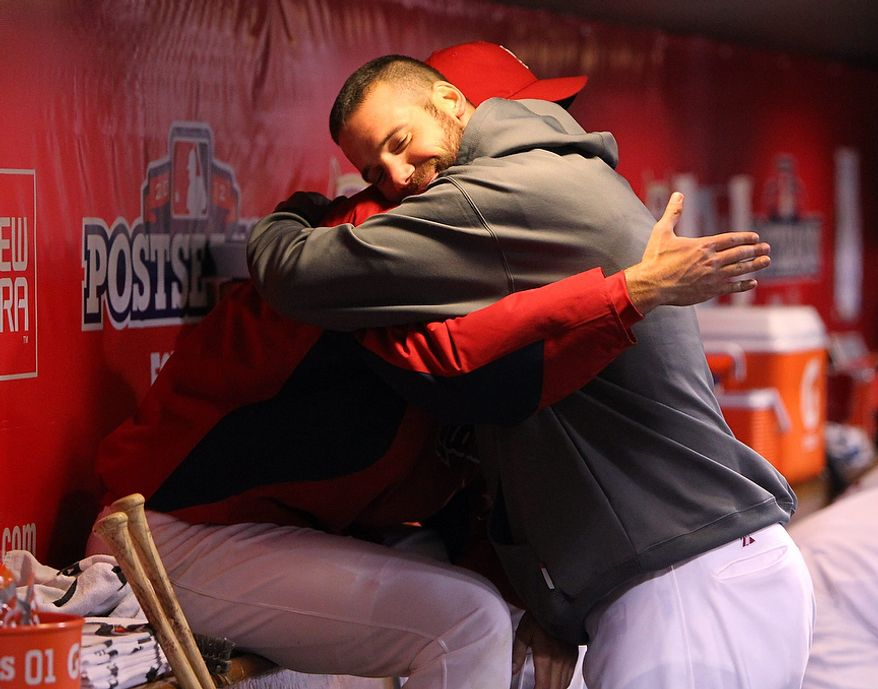 St. Louis Cardinals pitcher Chris Carpenter (facing) embraces teammate Adam Wainwright after Wainwright pitched seven innings and allowed only one run during Game 4 of the National League Championship Series between the Cardinals and the San Francisco Giants on Oct. 18, 2012, in St. Louis. (Associated Press/St. Louis Post-Dispatch)
