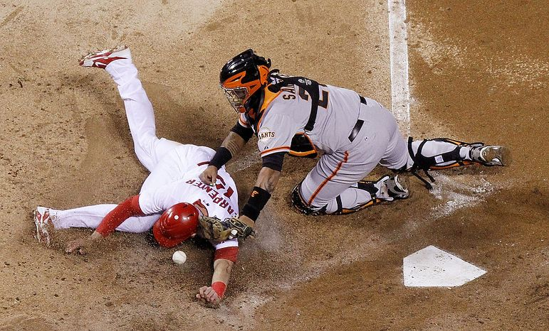 San Francisco Giants catcher Hector Sanchez (right) is unable to handle the throw as St. Louis Cardinals 1B Matt Carpenter slides towards home on a single by Matt Holliday in the fifth inning of Game 4 of the National League Championship Series on Oct. 18, 2012, in St. Louis. (Associated Press/St. Louis Post-Dispatch)