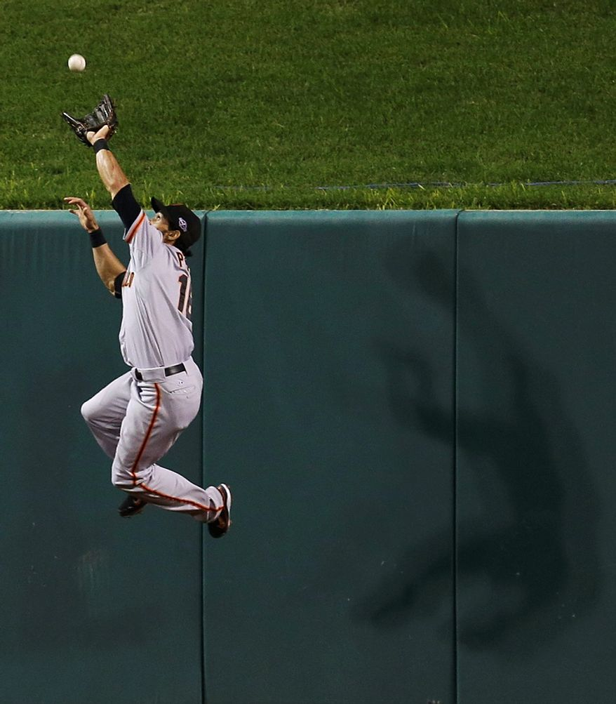 San Francisco Giants' Angel Pagan goes up to catch a fly ball hit by St. Louis Cardinals' Yadier Molina in the third inning of Game 4 of the National League Championship Series on Oct. 18, 2012, in St. Louis. (Associated Press)