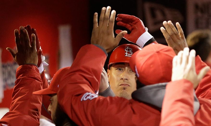 St. Louis Cardinals OF Allen Craig is congratulated after hitting sacrifice fly to score Matt Carpenter from third during the first inning of Game 4 of the National League Championship Series against the San Francisco Giants on Oct. 18, 2012, in St. Louis. (Associated Press)