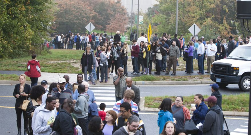 Thousands of supporters of President Obama wait in a light rain along a path through the George Mason University campus in Fairfax, Va., before a Oct. 19, 2012, campaign event on the campus. (Craig Bisacre/The Washington Times)