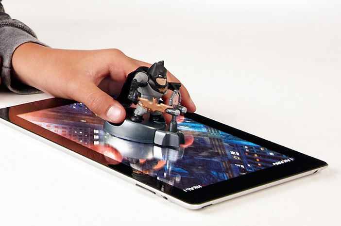 Use two fingers on the display base to have the Caped Crusader action figure interact with the iPad game using the Apptivity Batman: The Dark Knight Rises starter set.