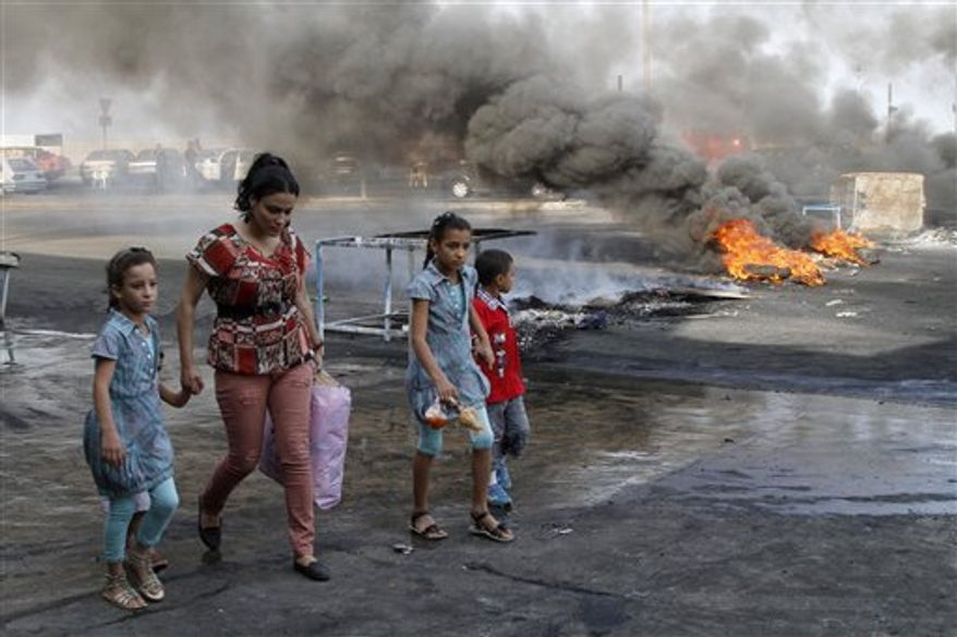 A family walks past flaming tires used as a roadblock to protest the death of Brig. Gen. Wissam al-Hassan, head of the intelligence division of Lebanon's domestic security forces in a car bomb attack targeting his convoy, in the southern port city of Sidon, Lebanon, Saturday, Oct. 20, 2012. (AP Photo/ Mohammed Zaatari)