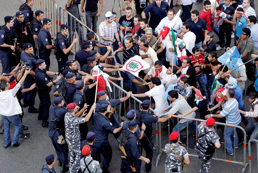 Police and protesters clash after the funeral of Brig. Gen. Wissam al-Hassan in Beirut on Sunday. Clashes erupted after the funeral for Gen. al-Hassan, who was a powerful opponent of Syria in Lebanon. He was buried in Martyrs Square in Beirut near former Prime Minister Rafik Hariri, who was killed in 2005. (Associated Press)