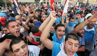 Protesters chant slogans against the Lebanese government in Beirut on Sunday, Oct. 21, 2012, after the funeral of Brig. Gen. Wissam al-Hassan, who was assassinated on Friday in a car bombing. (AP Photo/Bilal Hussein)
