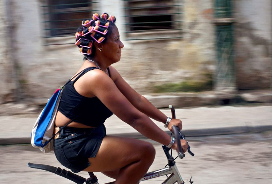 A woman wearing hair curlers rides her bike through Old Havana, Cuba, Saturday, Oct. 20, 2012. On Sunday, Cubans will cast ballots to choose among candidates for municipal assemblies that administer local governments and relay complaints on issues such as potholes and housing, social and sports programs. (AP Photo/Ramon Espinosa)