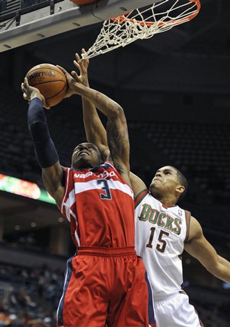 Washington Wizards' Bradley Beal (3) shoots over Milwaukee Bucks' Tobias Harris (15) during the first half of an NBA preseason basketball game, Saturday, Oct. 20, 2012, in Milwaukee. (AP Photo/Jim Prisching)