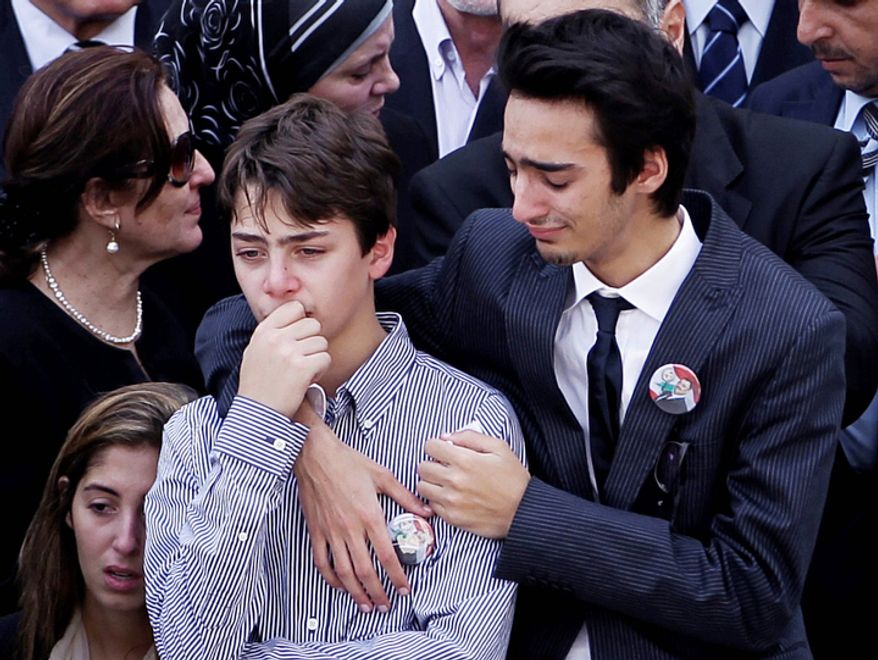 The two sons of Brig. Gen. Wissam al-Hassan, who was assassinated on Friday by a car bomb, mourn during their father's funeral procession at the Lebanese police headquarters in Beirut, Lebanon, Sunday Oct. 21, 2012. Lebanese soldiers fired guns and tear gas to push back hundreds of protesters who broke through a police cordon and tried to storm the government headquarters in Beirut. The enraged crowd came from the funeral of a top Lebanese intelligence official assassinated in a massive car bombing.(AP Photo/Hussein Malla)