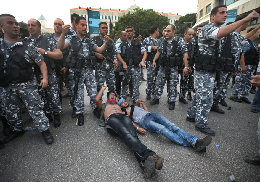 Lebanese protesters lie on the road in front of police during clashes after the funeral of Brig. Gen. Wissam al-Hassan who was assassinated on Friday by a car bomb in Beirut, Lebanon, Sunday Oct. 21, 2012. Lebanese soldiers fired guns and tear gas to push back hundreds of protesters who broke through a police cordon and tried to storm the government headquarters in Beirut. The enraged crowd came from the funeral of a top Lebanese intelligence official assassinated in a massive car bombing. (AP Photo/Hussein Malla)