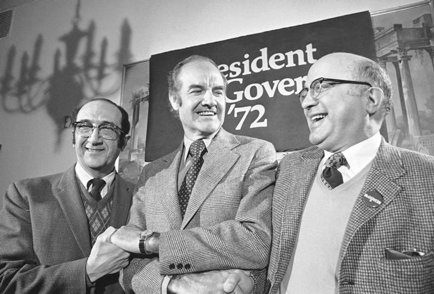In this Jan. 17, 1972 file photo, Sen. George McGovern, D-S.D., joins in a three way handshake with Salvador Luria, left, a Nobel Laureate in biology from Massachusetts Institute of Technology, and physicist Harry Palevsky of the Brookhaven National Laboratory of Long Island, N.Y., after they announced their support for his presidential campaign at a news conference in Boston.  A family spokesman says, McGovern, the Democrat who lost to President Richard Nixon in 1972 in a historic landslide, has died at the age of 90. (AP Photo/Bill Chaplis, File)