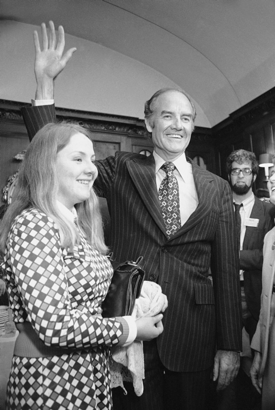 In this April 25, 1972 file photo, Sen. George S. McGovern, D-S.D., signals victory as he talks with the media as his daughter Teresa, stands by in Boston, after he won the Massachusetts  Democratic presidential primary. A family spokesman says, McGovern, the Democrat who lost to President Richard Nixon in 1972 in a historic landslide, has died at the age of 90. According to the spokesman,  McGovern died Sunday, Oct. 21, 2012 at a hospice in Sioux Falls, surrounded by family and friends.  (AP Photo)