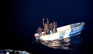 **FILE** This photo released by the French Navy shows pirates holding their hands up to soldiers (left) of the French vessel La Somme early Oct. 7, 2009, off the Somalia coast. Somali pirates in two skiffs fired on a French navy vessel after apparently mistaking it for a commercial boat, the French military said. The French ship gave chase and captured five suspected pirates. (Associated Press/Olivier Amalvict/ECPAD/French Navy)