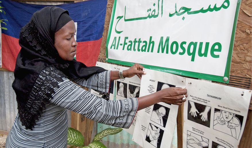 Darlene Derosier, 43, a Muslim convert since the 2010 earthquake in Haiti, posts a sign explaining Islamic cleansing rituals for prayer at the Al-Fattah Mosque in Gressier. The tradition of constant washing, she said, helps Muslims avoid cholera. (Associated Press)