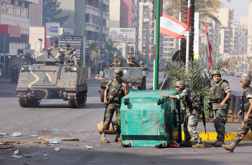 Lebanese Army soldiers remove garbage containers used as a roadblock in a neighborhood after overnight clashes between Sunni and Shiite gunmen in Beirut on Monday. Troops began a big operation in the capital aiming to open all closed roads and to force gunmen out of the streets. (Associated Press)