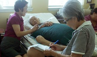 Frank Tanabe gets help from his daughter Barbara Tanabe (left) to fill out an absentee ballot in Honolulu while his wife, Setsuko Tanabe, sits in the foreground. Mr. Tanabe is a 93-year-old World War II veteran with an inoperable liver tumor. (Associated Press)