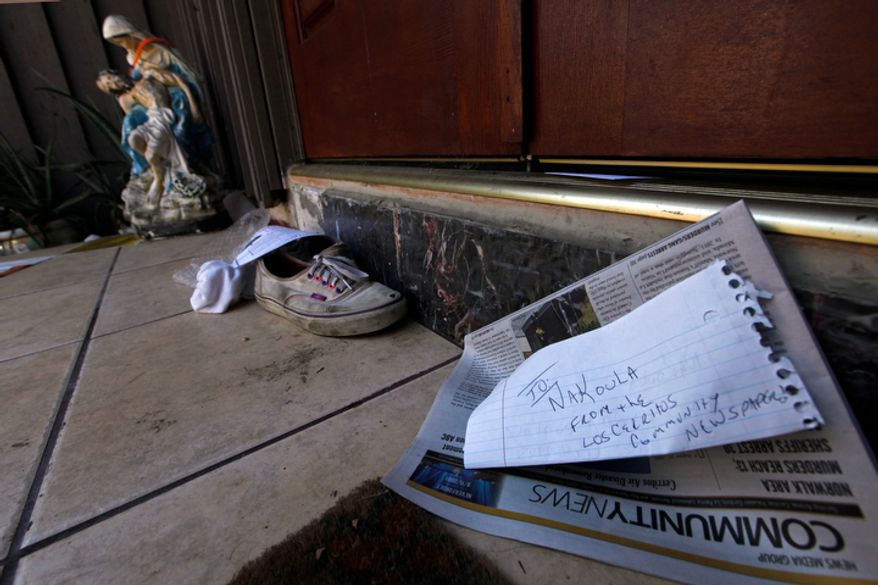 "A religious figure, shoes and a newspaper lie at the steps of the suburban Los Angeles home believed to be that of filmmaker Nakoula Basseley Nakoula, Friday, Sept. 14, 2012. Federal authorities have identified Nakoula, a self-described Coptic Christian, as the key figure behind ""Innocence of Muslims,"" a film denigrating Islam and the Prophet Muhammad that ignited mob violence against U.S. embassies across the Middle East. (AP Photo/Reed Saxon)"