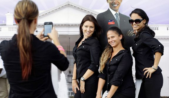 Workers pose for a photo with a life-sized cutout of President Barack Obama at a presidential debate fair on the campus of Lynn University, Monday, Oct. 22, 2012, in Boca Raton, Fla., where President Barack Obama and Republican presidential candidate and former Massachusetts Gov. Mitt Romney will hold their final debate. (AP Photo/Eric Gay)