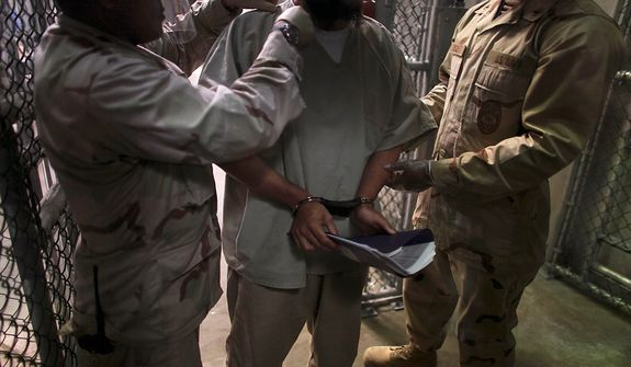 "In this photo, made through one way glass, reviewed by the U.S. military, a Guantanamo detainee is frisked before being transported by guards after attending a class in ""Life Skills,"" inside Camp 6 high-security detention facility at Guantanamo Bay U.S. Naval Base, Cuba, Tuesday, March 30, 2010. The Obama Administration is pushing to close the Guantanamo detention facility, by  transferring, prosecuting, or releasing the remaining detainees. (AP Photo/Brennan Linsley)"