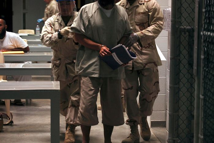 In this March 30, 2010, photo made through a one-way glass and reviewed by the U.S. military, a Guantanamo detainee carries a workbook while escorted by guards who wear rubber gloves and face masks after attending a life skills class in the Camp 6 high-security detention facility at the Guantanamo Bay U.S. Naval Base in Cuba. (AP Photo/Brennan Linsley)