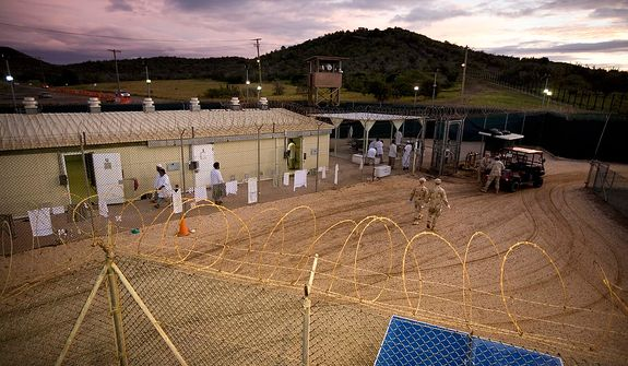 In this Nov. 18, 2008 file photo, reviewed by the U.S. Military, Guantanamo detainees, in white, and U.S. military guards walk around Camp 4 detention facility at the U.S. Naval Base, in Guantanamo Bay, Cuba. A U.S. appeals court reversed a ruling Wednesday, Feb. 18, 2009 that would have transferred 17 Guantanamo Bay detainees, none of whom are labeled enemy combatants, to the United States. (AP Photo/Brennan Linsley, File)
