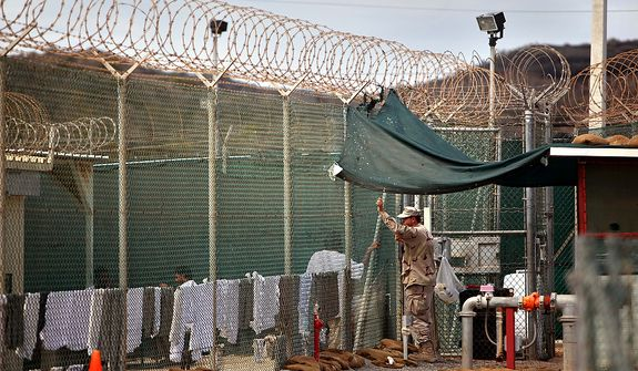 In this Jan. 21, 2009 file photo, reviewed by the U.S. Military, a guard talks to a Guantanamo detainee in the open yard in Camp 4 detention center on the U.S. Naval Base in Guantanamo Bay, Cuba. (AP Photo/Brennan Linsley, FILE)