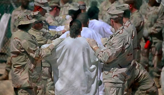In this photo, reviewed by the U.S. military, guards stand on either side of a line-up of Guantanamo detainees, in white, to perform a search for unauthorized items, at Guantanamo's Camp 4 detention facility, at Guantanamo Bay U.S. Naval Base, Cuba, Tuesday, May 12, 2009. (AP Photo/Brennan Linsley)