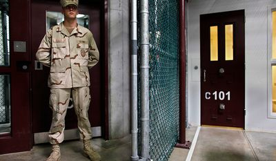 In this photo reviewed by the U.S. military, a guard stands in the Camp Six detention facility on Guantanamo Bay U.S. Naval Base in Cuba, Sunday, May 31, 2009. (AP Photo/Brennan Linsley, Pool)