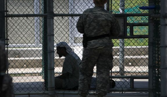 In this March 29, 2010 photo, reviewed by the U.S. military, photographed through one-way glass, a Guantanamo guard keeps watch over detainees during recreation time at Camp 5 high-security detention facility at Guantanamo Bay U.S. Naval Base, Cuba. The Obama Administration is pushing to close the Guantanamo detention facility, by  transferring, prosecuting, or releasing the remaining detainees. (AP Photo/Brennan Linsley)