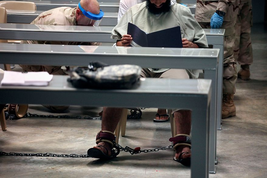 """In this photo, made through one way glass, reviewed by the U.S. military, a shackled Guantanamo detainee reads his materials as he attends a class in """"Life Skills,"""" as guards in the background shackle another detainee to the floor after bringing him to the class, inside Camp 6 high-security detention facility at Guantanamo Bay U.S. Naval Base, Cuba, Tuesday, March 30, 2010. The Obama Administration is pushing to close the Guantanamo detention facility, by  transferring, prosecuting, or releasing the remaining detainees. (AP Photo/Brennan Linsley)"""