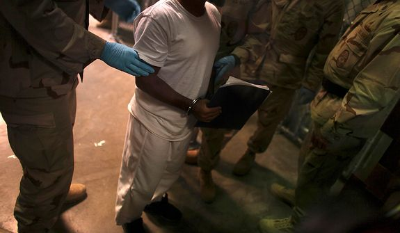 In this March 30, 2010 photo made through one way glass and reviewed by the U.S. military, a Guantanamo detainee carries a workbook while escorted by guards after attending Life Skills class in Camp 6 high-security detention facility on Guantanamo Bay U.S. Naval Base in Cuba. The Obama administration is pushing to close the Guantanamo detention facility by transferring, prosecuting or releasing the remaining detainees. (AP Photo/Brennan Linsley)