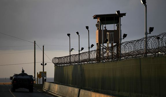 ** FILE ** In this March 30, 2010, photo reviewed by the U.S. military, a U.S. trooper stands in the turret of a vehicle with a machine gun, left, as a guard looks out from a tower at the detention facility on Guantanamo Bay U.S. Naval Base in Cuba. (AP Photo/Brennan Linsley)