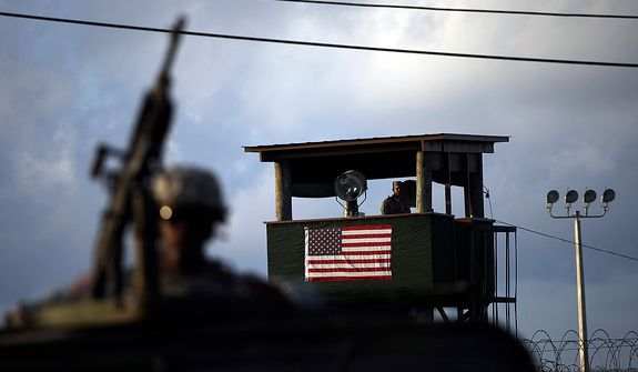 In this March 30, 2010 photo, reviewed by the U.S. military, a U.S. trooper mans a machine gun in the turret on a vehicle as a guard looks out from a tower in front of the detention facility at Guantanamo Bay U.S. Naval Base, Cuba. The Obama Administration is pushing to close the Guantanamo detention facility, by  transferring, prosecuting, or releasing the remaining detainees. (AP Photo/Brennan Linsley)