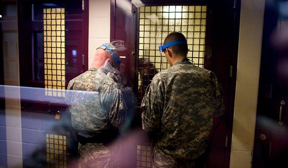 In this image reviewed by the U.S. Military, a Guantanamo detainee peers through the steel grate in a room as guards prepare to open the door at the Camp 5 detention facility on the U.S. Naval Base in Guantanamo Bay, Cuba, Wednesday, Nov. 19, 2008.  By January, some detainees will have been locked up on this U.S. military base in Cuba for seven years. President-elect Barack Obama has vowed to close the detention center at Guantanamo and is weighing what to do with the roughly 250 foreigners who are being held.  (AP Photo/Brennan Linsley)