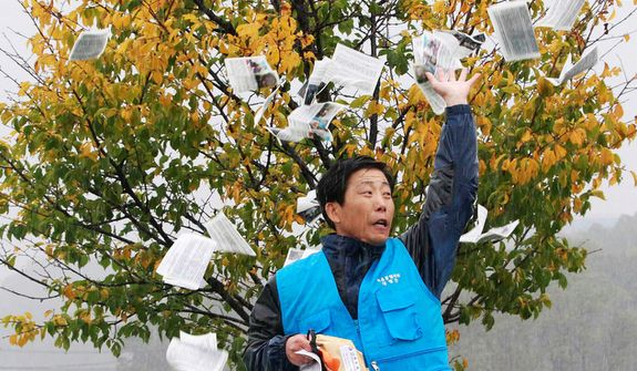North Korean defector Park Sang-hak hurls anti-North Korea leaflets as police block his planned rally on a road in Paju, near the Demilitarized Zone, in South Korea on Monday, Oct. 22, 2012. South Korea banned activists from launching the propaganda leaflets to North Korea after the North threatened to attack. (AP Photo/Ahn Young-joon)