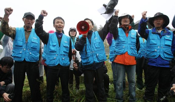North Korean defectors shout slogans as police officers block their planned rally on a road in Paju, near Demilitarized Zone, in South Korea, on Monday, Oct. 22, 2012. South Korea has banned activists from launching propaganda leaflets to North Korea after the North threatened to attack. (AP Photo/Ahn Young-joon)