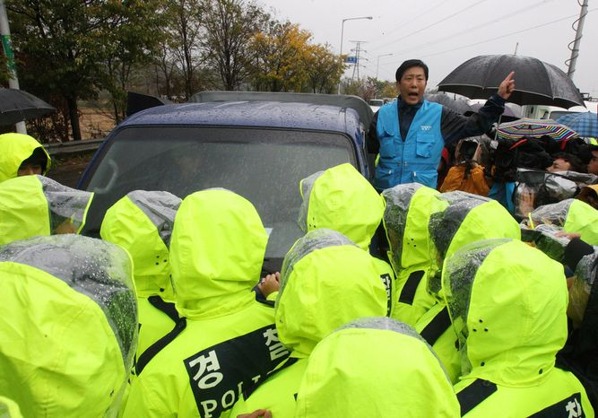 North Korean defector Park Sang-hak protests as police block his planned rally on a road in Paju, near the demilitarized zone, in South Korea on Monday, Oct. 22, 2012. South Korea has banned activists from launching propaganda leaflets into North Korea after the North threatened to attack. (AP Photo/Ahn Young-joon)