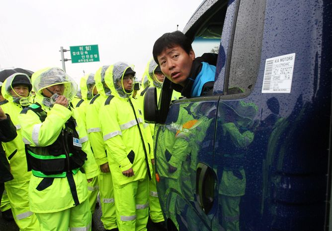 Police officers block an activist in a car carrying anti-North Korea leaflets in Paju, near the Demilitarized Zone, in South Korea on Monday, Oct. 22, 2012. South Korea banned the activists Monday from entering a border area where they planned to launch anti-Pyongyang leaflets into North Korea, an unusual move that the activists likened to surrender. (AP Photo/Ahn Young-joon)