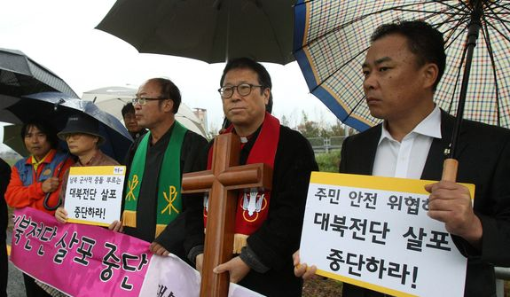 "Pro-North Korean activists stage a rally to stop the sending of anti-North Korea leaflets across the border on the road in Paju, near the Demilitarized Zone, in South Korea on Monday, Oct. 22, 2012. North Korea's military warned last week that it would strike if South Korean activists carried through with their plan to fly balloons carrying the propaganda leaflets across the border. South Korea pledged to retaliate if it was attacked.  The placards translate as ""Stop sending anti-North Korea leaflets."" (AP Photo/Ahn Young-joon)"