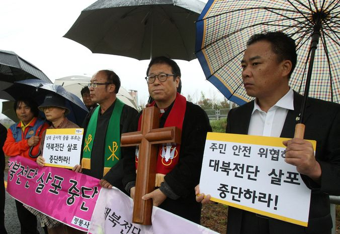 """Pro-North Korean activists stage a rally to stop the sending of anti-North Korea leaflets across the border on the road in Paju, near the Demilitarized Zone, in South Korea on Monday, Oct. 22, 2012. North Korea's military warned last week that it would strike if South Korean activists carried through with their plan to fly balloons carrying the propaganda leaflets across the border. South Korea pledged to retaliate if it was attacked.  The placards translate as """"Stop sending anti-North Korea leaflets."""" (AP Photo/Ahn Young-joon)"""