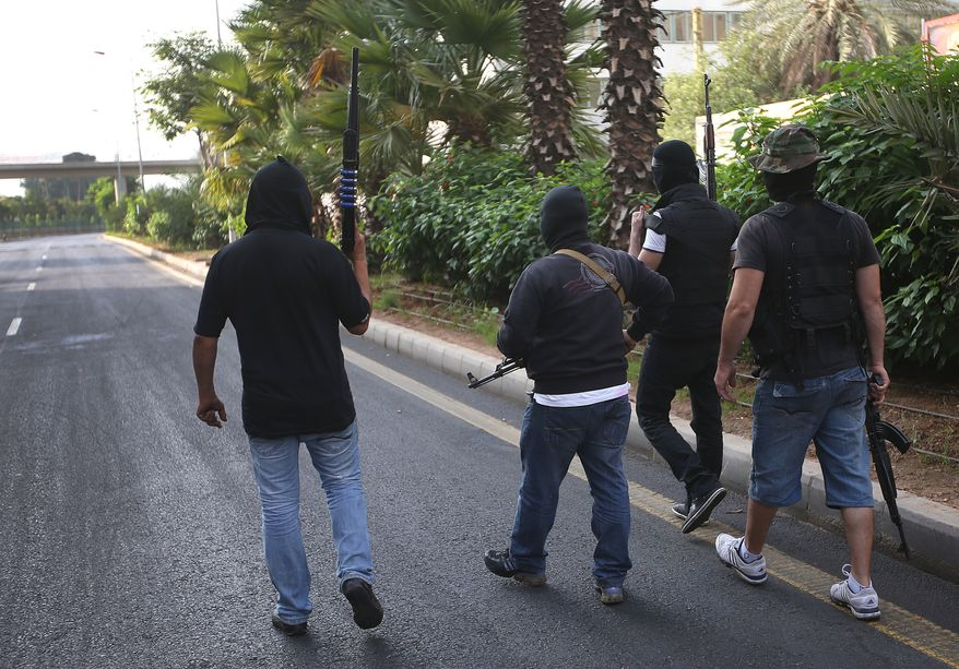 Sunni gunmen patrol an empty street leading to a Shiite neighborhood in Beirut on Monday, Oct. 22, 2012, after overnight clashes between Sunni and Shiite gunmen. (AP Photo/Hussein Malla)